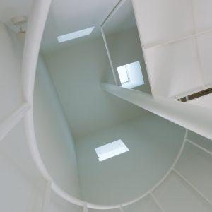 互い違いの内壁/homeHR 階段室を見上げる