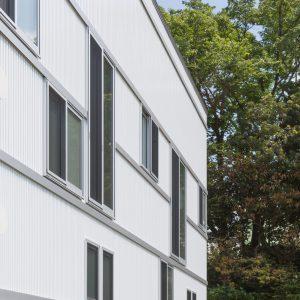 六層二階建ての窓/リナスト障がい者福祉施設 敷地の南側には神社の杜が広がる