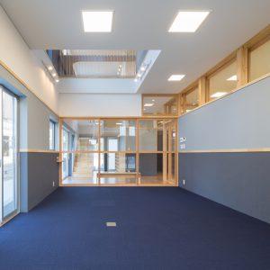 六層二階建ての窓/リナスト障がい者福祉施設 事務室からエントランスホールを見る