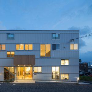 六層二階建ての窓/リナスト障がい者福祉施設 北側正面外観夕景