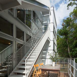 六層二階建ての窓/リナスト障がい者福祉施設 南側ウッドデッキと屋外階段