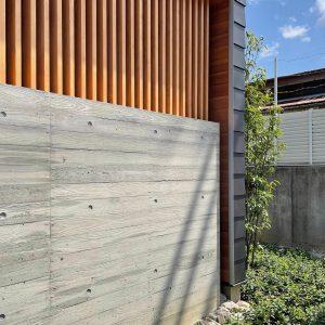 直方体と門型の庇 木製縦ルーバーと杉型枠のコンクリート打放し壁