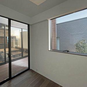 直方体と門型の庇 子ども室/左側に窓を挟んでウッドデッキとリビングが見える