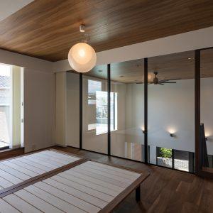 直方体と門型の庇 主寝室/左側に屋上テラス、右側にリビング上部の吹抜けを見る