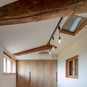 天井裏の明るさ/homeSK 新設された小屋の内部/丸太の梁が一部に露出している